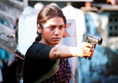 Image of an Indian woman with a determined expression on her face and a handgun in her hand.