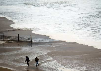 People walk near a surf from Hurricane Sandy rising past sand fences onto the beach in Ocean City, Maryland 