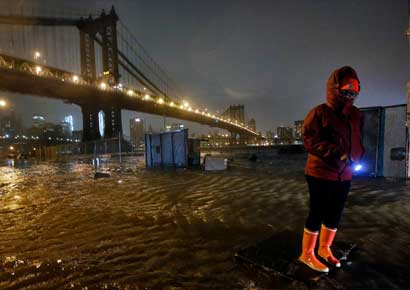 A local resident navigates the flooded streets of the DUMBO neighborhood of Brooklyn, New York