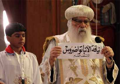 Egyptian caretaker of the Coptic Church, interim Pope Bakhomious (R) holds a piece of paper with the name of Bishop Tawadros written on it, after it was picked by Bishoy Gerges in Cairo
