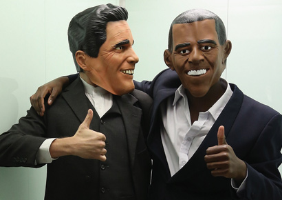 Actors wearing Mitt Romney (L) and Barack Obama masks stand in an elevator while attending a U.S. election party at the Bertelsmann Foundation on November 6, 2012.