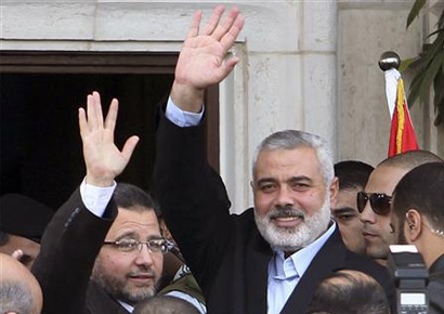Egyptian prime minister Hisham Kandil (L) and senior Hamas leader Ismail Haniyeh wave to people in Gaza City on Friday.