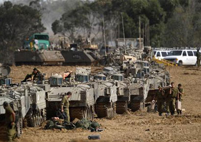Israeli soldiers prepare armoured personnel carriers (APCs) at an area near the border with the Gaza Strip on Friday.