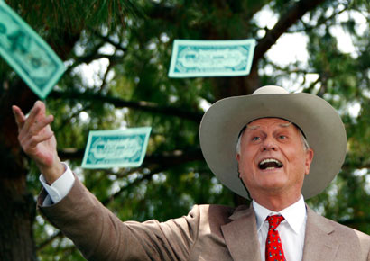 Actor Larry Hagman throws fake dollars notes during a photocall at the 50th Monte Carlo television festival in Monaco on June 8, 2010 file photo.