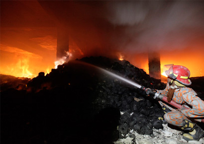 A fireman struggles to bring the fire at a garment factory under control near Dhaka early on Sunday.