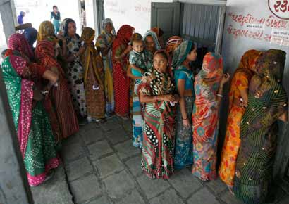 Women stand in a queue to cast their ballots outside a polling booth during the first phase of state elections in Sanand