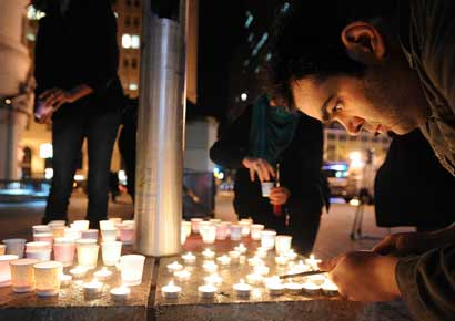 People light candles during a vigil commemorating victims of a Connecticut elementary school shooting in Oakland, California. Twenty six schoolchildren were slaughtered by a heavily armed gunman who opened fire at a suburban elementary school in Connecticut on Friday.