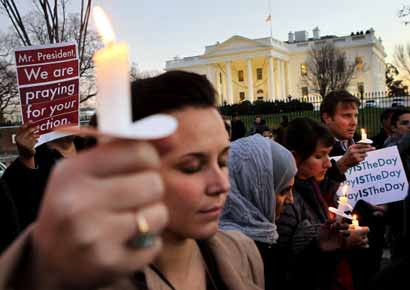 People gather outside the White House to participate in a candle light vigil to remember the victims at the Sandy Hook Elementary School shooting in Newtown, Connecticut.