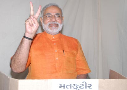 Narendra Modi gestures as he casts his vote during the second phase of state elections in Ahmedabad