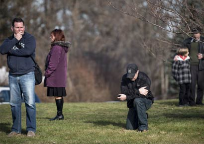 A man kneels as a funeral procession of one of the victims of the Newtown school shooting passes by.