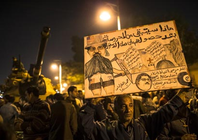An Egyptian protester opposed to president Mohamed Mursi holds up a placard during a demonstration at the Presidential Palace in Cairo on December 18, 2012.