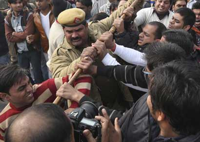 A policeman tries to stop demonstrators in front of the India Gate during a protest