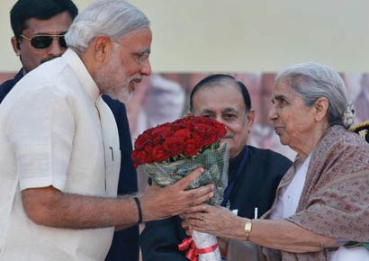 Governor of Gujarat, presents a bouquet to Narendra Modi after he took his oath as chief minister of Gujarat in the swearing-in ceremony