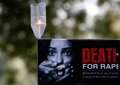 A candle is seen on a placard during a protest in New Delhi.