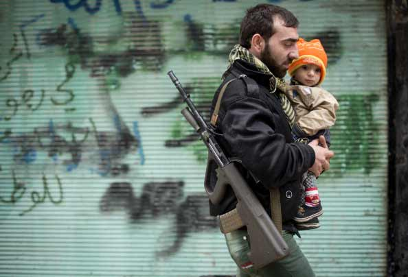 A rebel fighter carries his son after the Friday prayer in the al-Fardos neighbourhood of Aleppo on December 7, 2012.