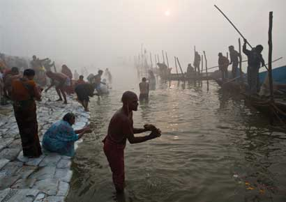 Hindu devotees take a holy dip in the waters of river Ganges amid fog ahead of the Kumbh Mela