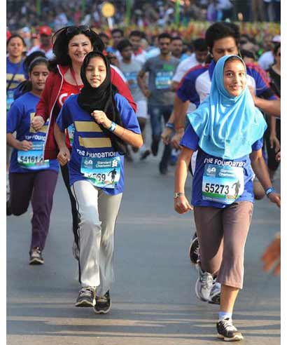 Two school girls pick up pace in the Mumbai Marathon 2013 on Sunday.