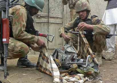 Security officials collect weapons near the site of a police station after it was attacked by militants in Bannu in northwestern Pakistan.