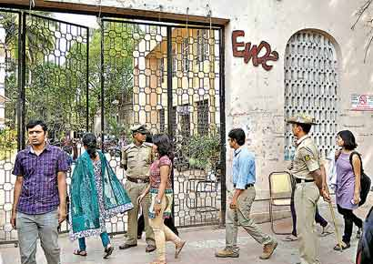Students entering the Bangalore Medical College on Monday as policemen stand guard at the entrance of the institution.
