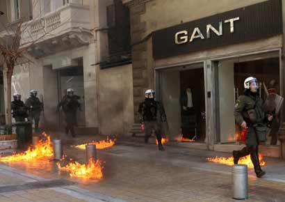 Riot police run by closed shops after protesters threw a petrol bomb following an anti-austerity march during a 24-hour strike in Athens on Wednesday.