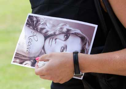 A mourner carries Reeva Steenkamp's picture