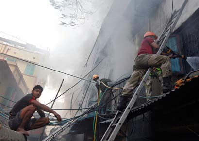 Fire fighters try to extinguish a fire at a multi-storey market complex in Kolkata