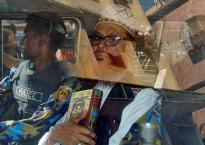 Delwar Hossain Sayedee (R), 73, vice-president of the Jamaat-e-Islami party, sits inside a vehicle next to a police officer on his way to a court in Dhaka, Bangladesh on Thursday. A Bangladesh tribunal sentenced an Islamist party leader to death on Thursday, the third verdict by the court set up to investigate abuses during the country`s independence war, and 15 people were killed in protests by his supporters. Sayedee was found guilty of charges of mass killing, rape, arson, looting and forcing minority Hindus to convert to Islam during the 1971 war of independence from Pakistan.