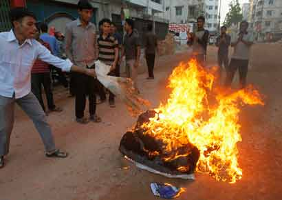 Activists from Bangladesh's Jamaat-e-Islami set fire to a pile of cotton material on a street during a strike to protest against the decision by the country's war crimes tribunal to deliver judgement in the cases involving their top leaders in Dhaka on March 3.