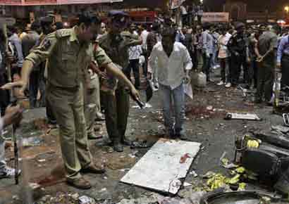 Police officers examine the site of an explosion at Dilsukh Nagar, in Hyderabad.