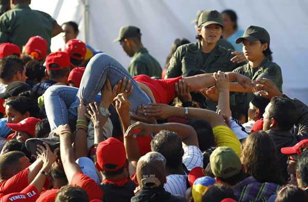 A supporter of Venezuela's late President Hugo Chavez is lifted out of the crowd after fainting while waiting for a chance to view his body in state, at the military academy in Caracas March 8, 2013. Chavez will be embalmed and put on display 