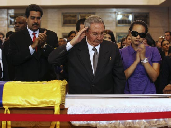 Cuba's President Raul Castro salutes the body of late Venezuelan President Hugo Chavez, which is lying in state, as he visits the wake with Chavez's daughter, Rosa Virginia (R), and Venezuela's Vice-President Nicolas Maduro (2nd L) at the military academy in Caracas March 7, 2013, in this picture provided by the Miraflores Palace. Chavez will be embalmed and put on display