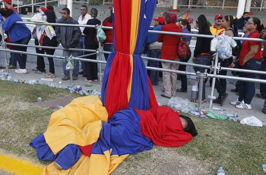 A supporter of Venezuela's late President Hugo Chavez sleeps after having spent the entire night waiting for a chance to view his body at the military academy in Caracas March 8, 2013. Chavez will be embalmed and put on display