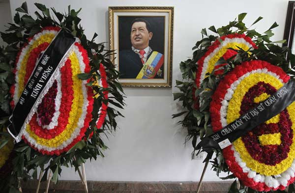 Wreaths from the Chinese embassy (L) and the Qatari embassy (R) are seen next to an image of Venezuela's late President Hugo Chavez at the Venezuelan embassy in Hanoi March 8, 2013. Ending one of Latin America's most remarkable populist rules, Chavez died on Tuesday at age 58 after a two-year battle with cancer that was first detected in his pelvis.