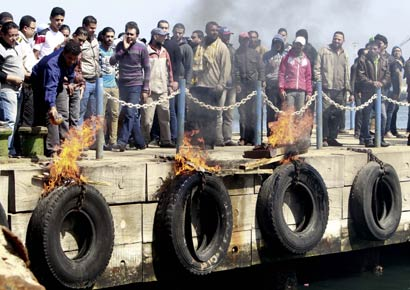 People against Egyptian President Mohamed Mursi burn tyres on the dock near the Suez Canal, in Port Said city.