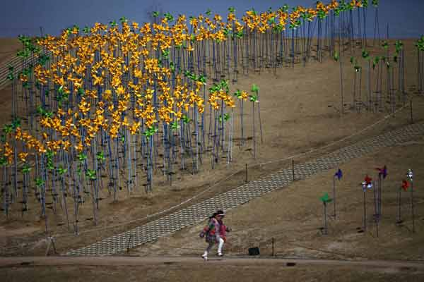 A girl runs past pinwheels arranged in the shape of the Korean peninsula at Imjingak pavillion near the demilitarized zone (DMZ) which separates the two Koreas in Paju, north of Seoul.