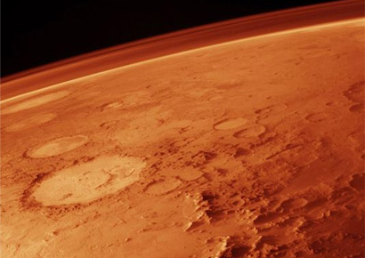 The tenuous atmosphere of Mars, visible on the horizon in this low-orbit photo