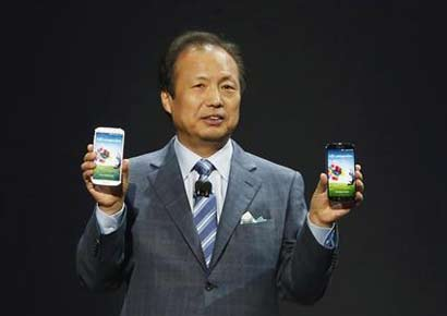 JK Shin, President and Head of IT and Mobile Communication Division, holds up Samsung's latest Galaxy S4 phones during its launch at the Radio City Music Hall in New York.