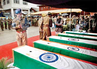 A soldier prays near the coffins of his colleagues at the police headquarters in Srinagar on Wednesday.