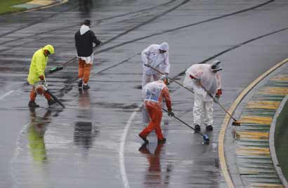 Marshals remove excess water on the track before the qualifying session of the Australian F1 Grand Prix at the Albert Park circuit in Melbourne 