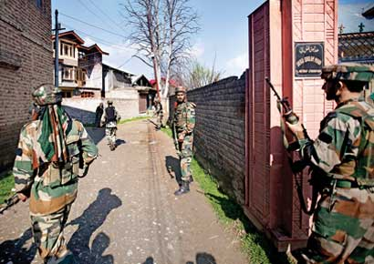Soldiers take position near the site of a shootout on the outskirts of Srinagar on Thursday.