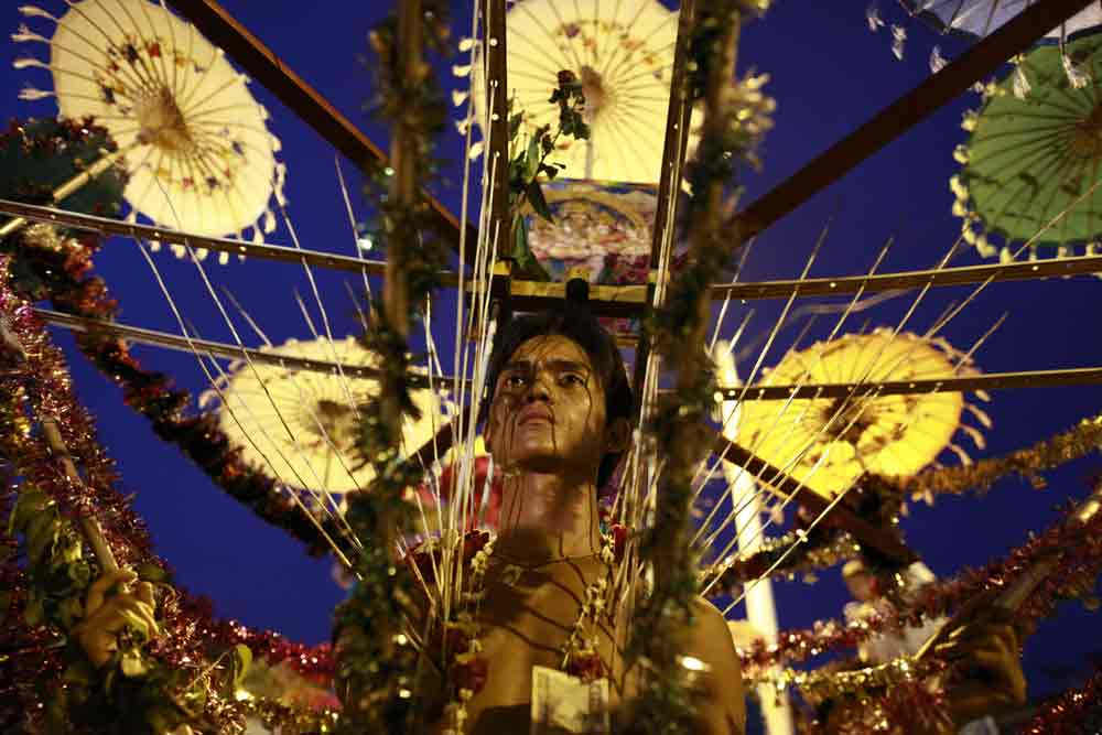 A Hindu devotee wearing a kavadi walks on hot coal during the anniversary celebrations of a Hindu temple in Yangon. Photo by Soe Zeya Tun