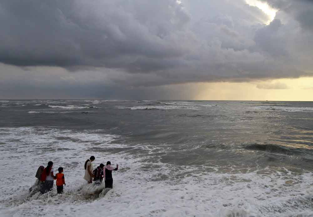 Beachgoers walk in the waters at Fort Kochi beach as clouds hover over the Arabian Sea in the southern Indian state of Kerala. Photo by Sivaram V