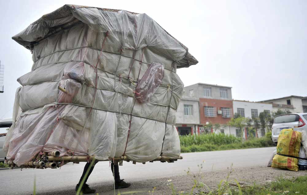 Liu Lingchao, 38, carries his makeshift dwelling as he walks along a road in Shapu township of Liuzhou, Guangxi Zhuang autonomous region. Photo by China Stringer
