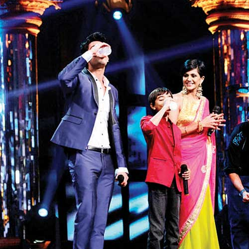 Karan Wahi and a contestant have milk as Mandira Bedi looks on.
