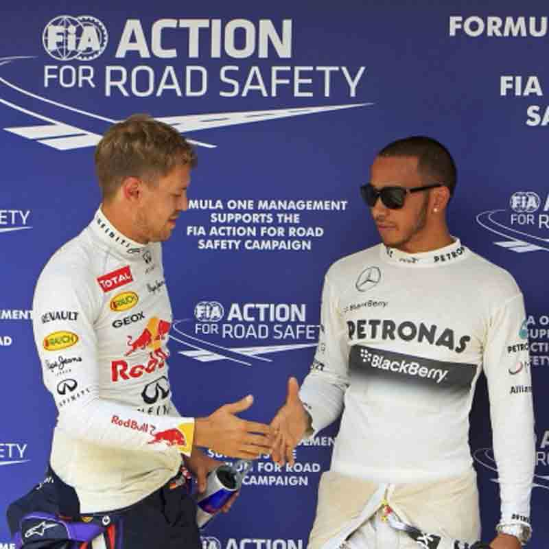 Mercedes Formula One driver Lewis Hamilton (C) of Britain shakes hands with Red Bull Formula One driver Sebastian Vettel (L) of Germany after the qualifying session of the Hungarian F1 Grand Prix at the Hungaroring circuit in Mogyorod, near Budapest.
