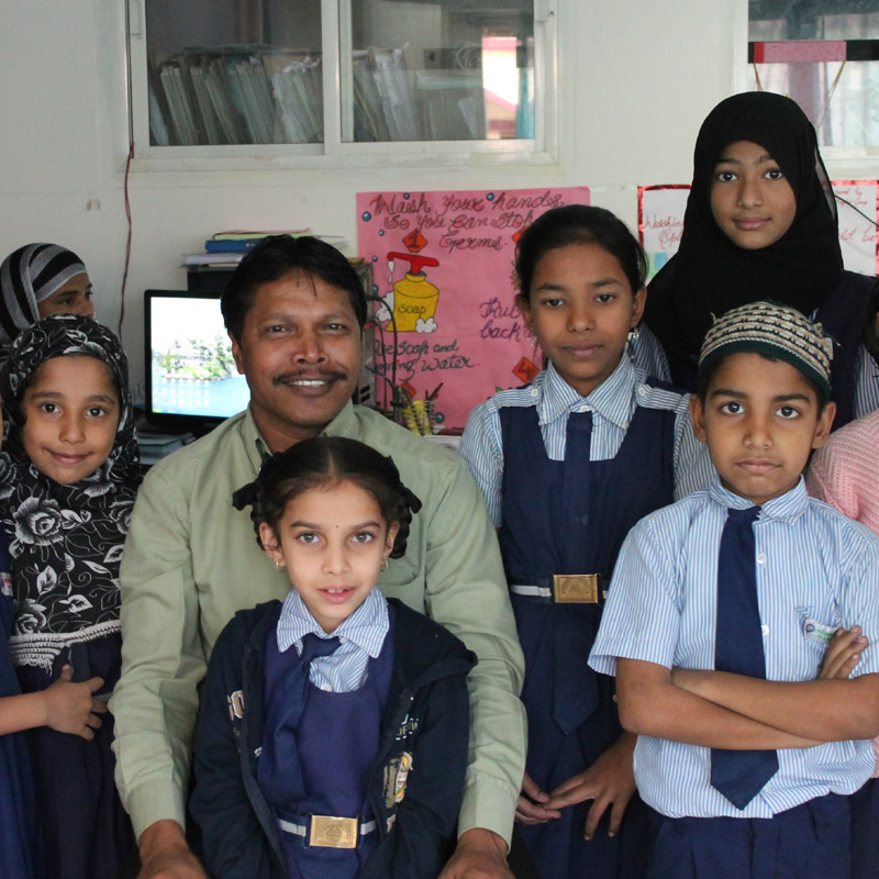 School leader Mohammed Anwar with his students. Anwar runs a chain of low-cost schools in Hyderabad serving 4000 kids in total, charging an average fee of ₹120 per month. Pictures courtsey India School Leadership Institute  (ISLI).